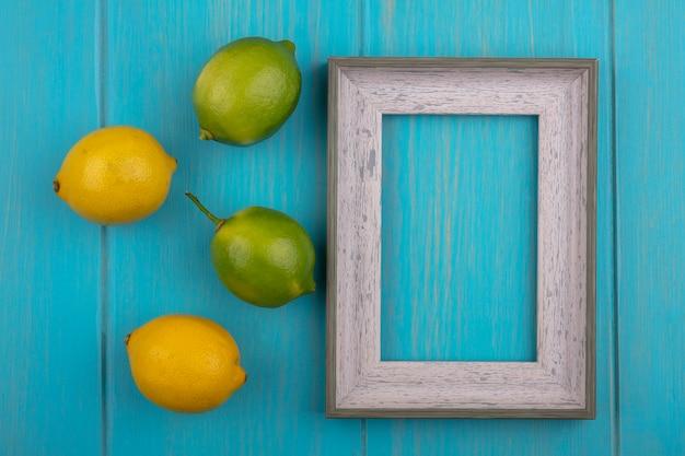 Bovenaanzicht kopie ruimte grijs frame met citroenen en limoenen (lemmetjes) op een turkooizen achtergrond
