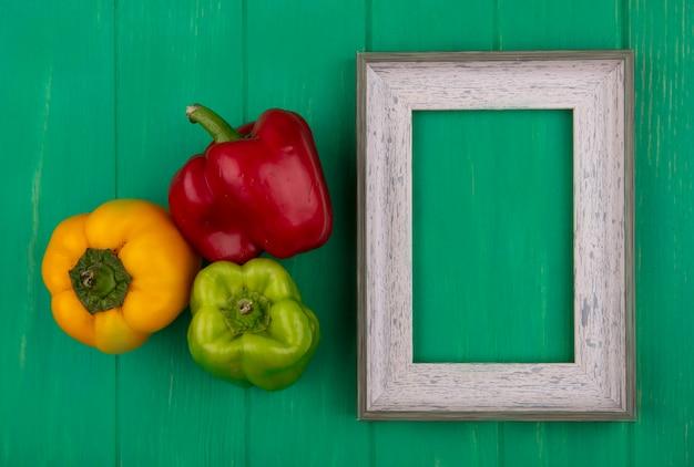 Bovenaanzicht kopie ruimte grijs frame met gekleurde paprika op groene achtergrond