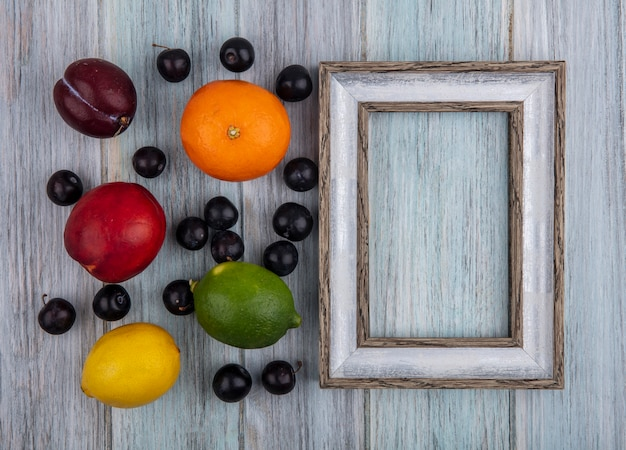 Bovenaanzicht kopie ruimte grijs frame met kersen pruim oranje perzik pruim citroen en limoen op grijze achtergrond
