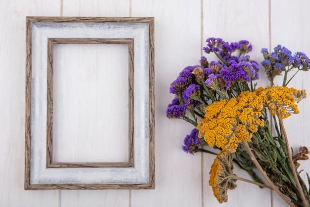 Bovenaanzicht kopie ruimte grijs frame met violet gele wilde bloemen op witte achtergrond