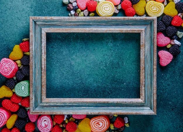 Bovenaanzicht kopie ruimte groen-gouden frame met veelkleurige marmelade in verschillende vormen met steenvormige chocolaatjes op een donkergroene achtergrond