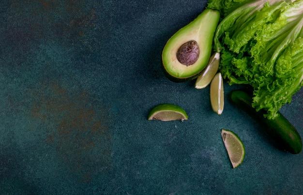 Bovenaanzicht kopie ruimte groenten van avocado-citroen komkommer en sla op een donkergroene achtergrond