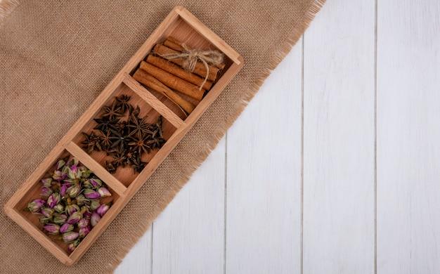 Bovenaanzicht kopie ruimte kaneel met kruidnagel en gedroogde rozenknoppen op een houten standaard op een grijze achtergrond