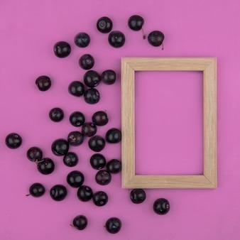 Bovenaanzicht kopie ruimte kersenpruim met frame op roze achtergrond