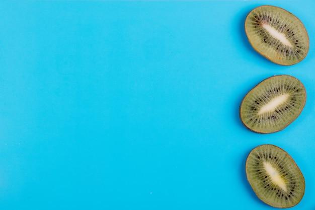 Bovenaanzicht kopie ruimte kiwi segmenten op een blauwe achtergrond