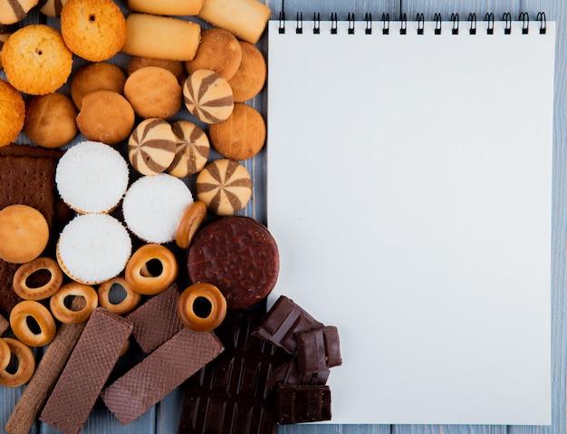 Bovenaanzicht kopie ruimte koekjesmix met wafels chocolade en een witte notebook