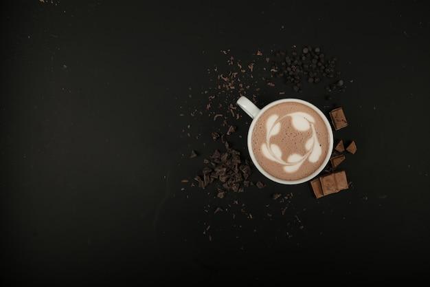 Bovenaanzicht kopie ruimte kopje cappuccino met chocolade op zwarte tafel