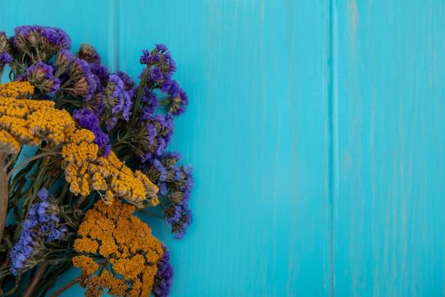 Bovenaanzicht kopie ruimte lila gele wilde bloemen op turkooizen achtergrond