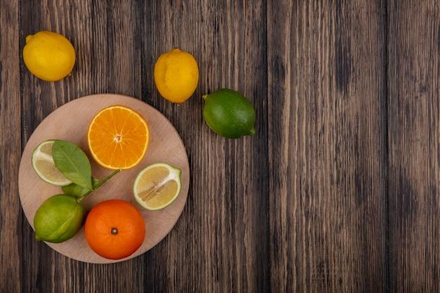 Bovenaanzicht kopie ruimte limoen helften met oranje helft op stand met citroenen op houten achtergrond