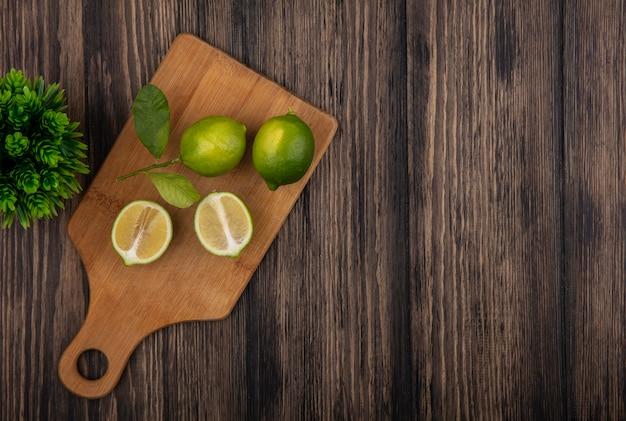 Bovenaanzicht kopie ruimte limoen helften op snijplank op houten achtergrond