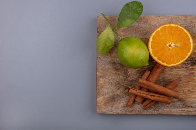 Bovenaanzicht kopie ruimte limoen met schijfje sinaasappel en kaneel op een snijplank op een grijze achtergrond