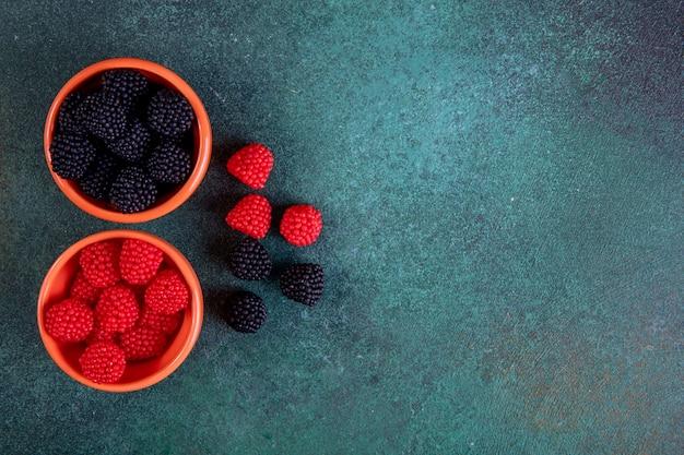 Bovenaanzicht kopie ruimte marmelade in de vorm van frambozen en bramen in schoteltjes voor jam op een donkergroene achtergrond