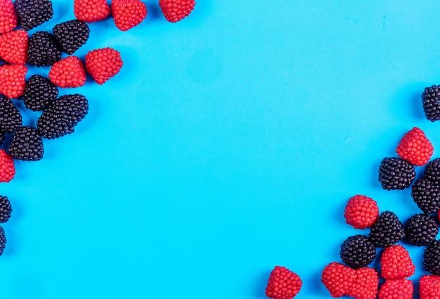 Bovenaanzicht kopie ruimte marmelade in de vorm van frambozen en bramen op een blauwe achtergrond