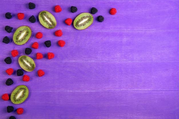 Bovenaanzicht kopie ruimte marmelade in formalines en bramen met kiwiplakken op een paarse achtergrond