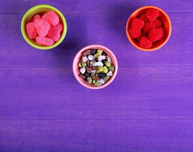 Bovenaanzicht kopie ruimte marmelade met chocolade stenen in schoteltjes voor jam op een paarse achtergrond