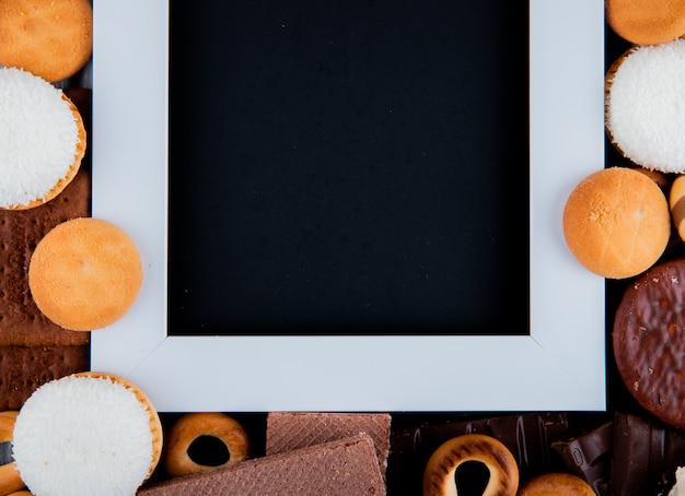 Bovenaanzicht kopie ruimte mix cookies met marshmallows en een wit frame met een zwarte achtergrond