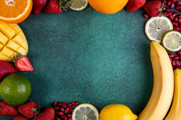 Bovenaanzicht kopie ruimte mix van fruit mango banaan aardbeien citroen oranje met frame op een groene achtergrond