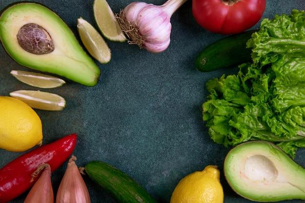 Bovenaanzicht kopie ruimte mix van groenten, avocado, citroen, tomaat, komkommers en sla op een donkergroene achtergrond