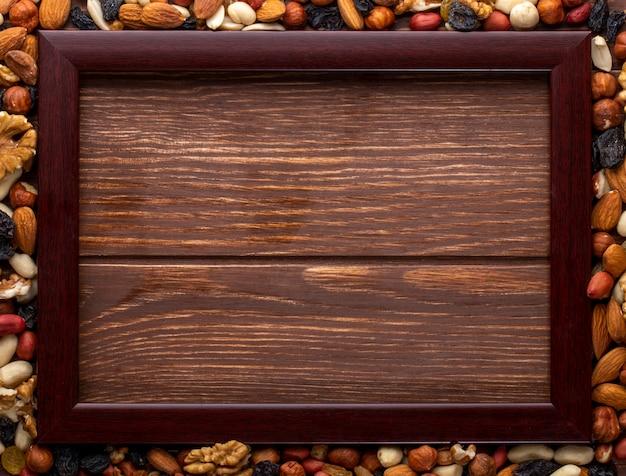 Bovenaanzicht kopie ruimte mix van noten met rozijnen en houten frame op een houten achtergrond