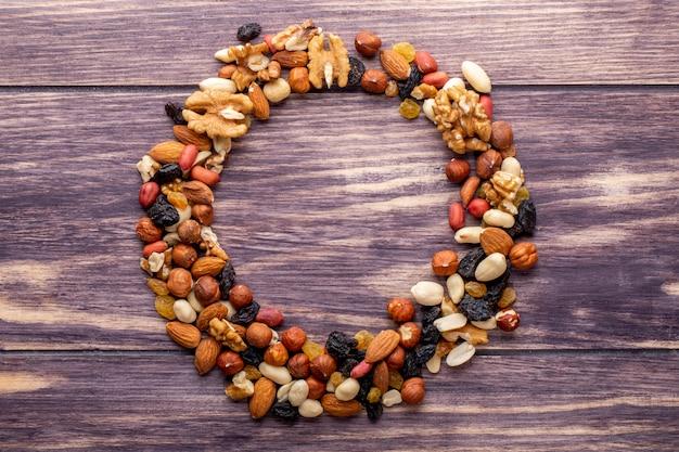 Bovenaanzicht kopie ruimte mix van noten met rozijnen in de vorm van een cirkel op een houten achtergrond