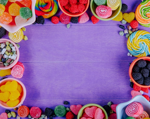 Bovenaanzicht kopie ruimte multi-gekleurde marmelade met chocolade stenen en gekleurde ijspegels in schoteltjes voor jam op een paarse achtergrond