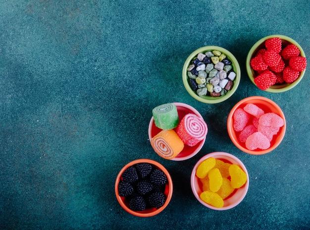Bovenaanzicht kopie ruimte multi-gekleurde marmelades in verschillende vormen in jam outlets op een donkergroene achtergrond
