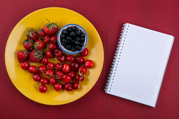 Bovenaanzicht kopie ruimte notebook met bosbessen aardbeien en kersen op een bord op een rode achtergrond