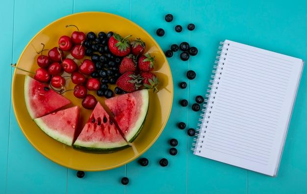 Bovenaanzicht kopie ruimte notitieboekje met plakjes watermeloen, aardbeien, kersen en bosbessen op een gele plaat op een lichtblauwe achtergrond