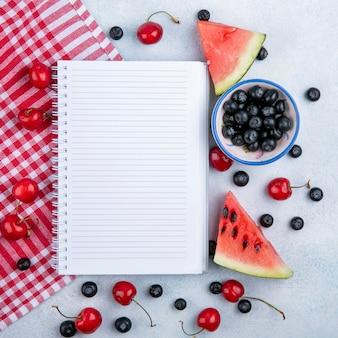 Bovenaanzicht kopie ruimte notitieboekje met plakjes watermeloen met kersen en bosbessen in een kopje