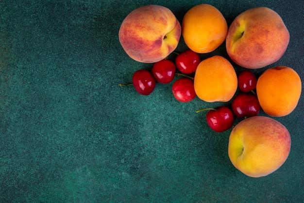 Bovenaanzicht kopie ruimte perziken met abrikozen en kersen op groen