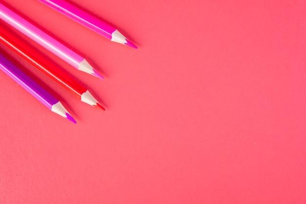 Bovenaanzicht kopie ruimte potloden van roze tinten op een roze achtergrond