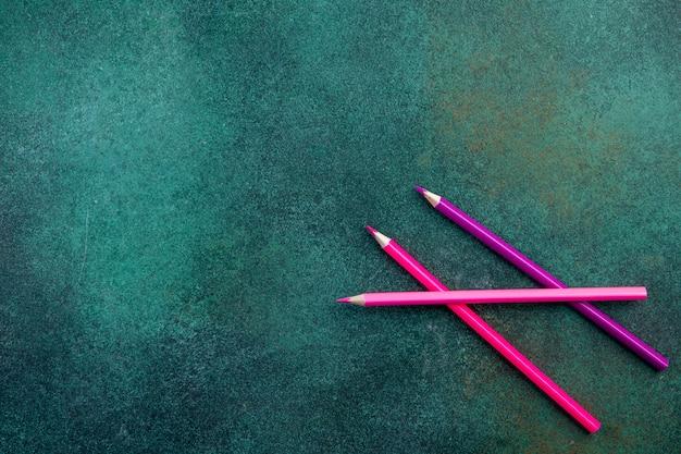 Bovenaanzicht kopie ruimte roze potloden op groene achtergrond