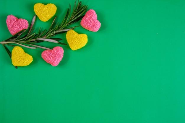 Bovenaanzicht kopie ruimte rozemarijntak met gele en roze marmelade op een groene achtergrond