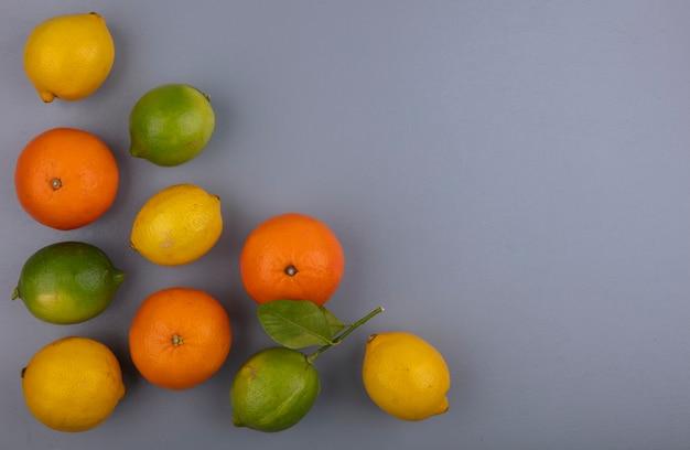 Bovenaanzicht kopie ruimte sinaasappelen met citroenen en limoenen op een grijze achtergrond