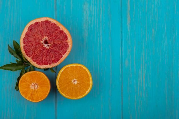 Bovenaanzicht kopie ruimte sinaasappelschijfje met grapefruitschijf op turkooizen achtergrond