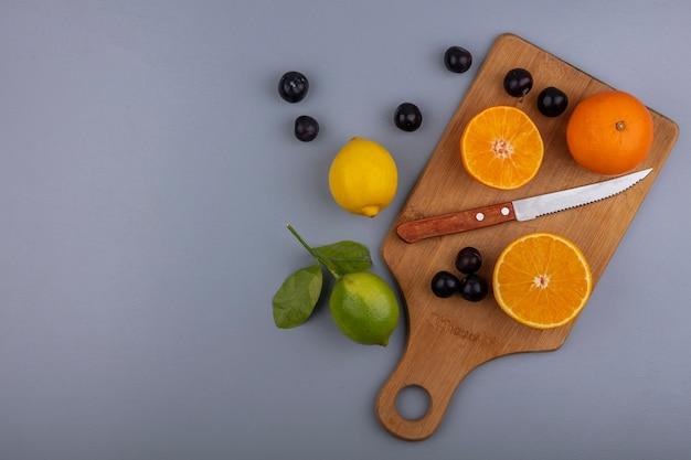 Bovenaanzicht kopie ruimte stukjes sinaasappel op snijplank met mes en kersenpruim citroen en limoen op grijze achtergrond