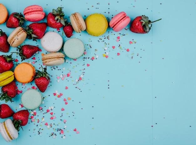 Bovenaanzicht kopie ruimte veelkleurige macarons met aardbeien op een blauwe achtergrond