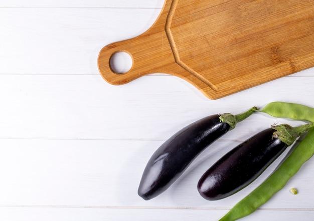 Bovenaanzicht kopie ruimte verse aubergine met groene lobby en snijplank op een witte achtergrond