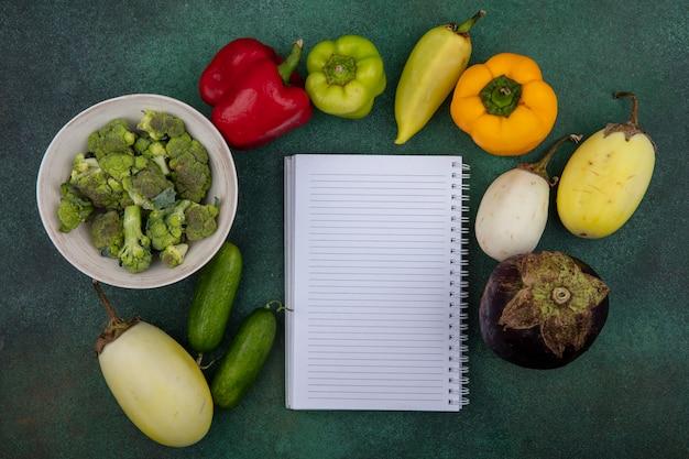 Bovenaanzicht kopie ruimte voorbeeldenboek met komkommers en paprika en broccoli op groene achtergrond