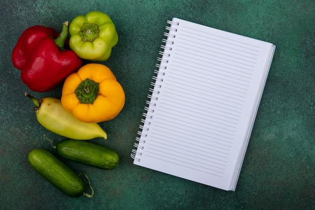 Bovenaanzicht kopie ruimte voorbeeldenboek met komkommers en paprika op groene achtergrond