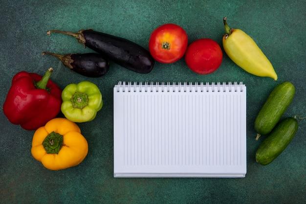 Bovenaanzicht kopie ruimte voorbeeldenboek met komkommers, paprika, tomaten en aubergines op een groene achtergrond