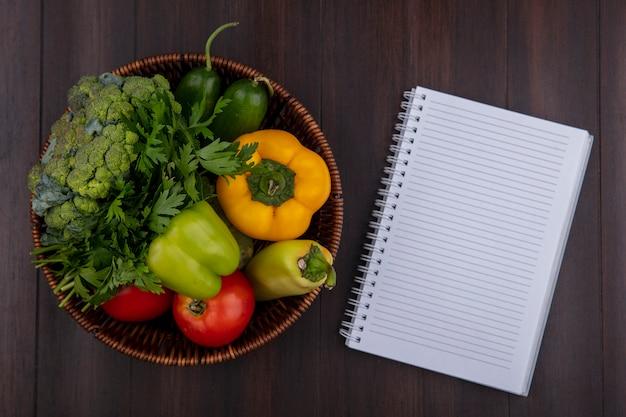 Bovenaanzicht kopie ruimte voorbeeldenboek met paprika, peterselie en tomaten in een mand op houten achtergrond