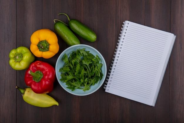 Bovenaanzicht kopie ruimte voorbeeldenboek met peterselie in een kom met komkommers en paprika op houten achtergrond