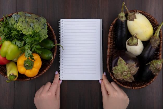 Bovenaanzicht kopie ruimte vrouw met voorbeeldenboek met paprika, peterselie en tomaten in een mand met aubergines op houten achtergrond
