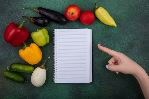 Bovenaanzicht kopie ruimte vrouw wijst naar voorbeeldenboek met komkommers, paprika, tomaten en aubergines op een groene achtergrond