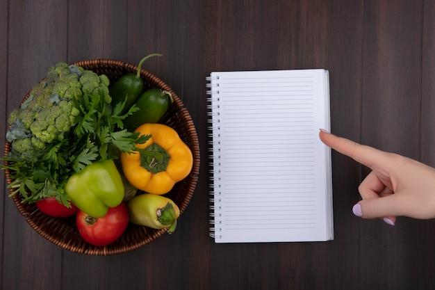 Bovenaanzicht kopie ruimte vrouw wijst naar voorbeeldenboek met paprika, peterselie en tomaten in een mand op houten achtergrond