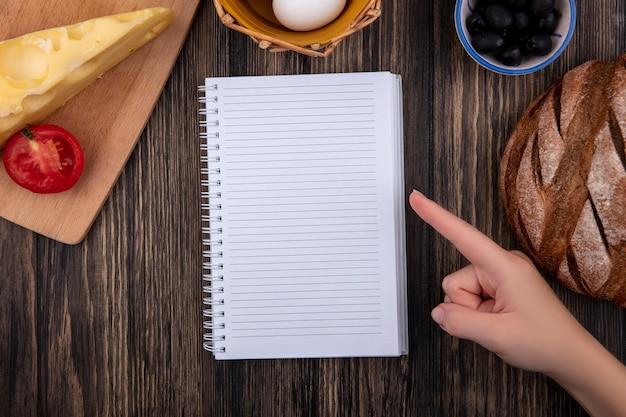 Bovenaanzicht kopie ruimte vrouw wijst naar voorbeeldenboek met zwarte olijven met tomaat, zwart brood en kaas op houten achtergrond