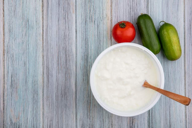 Bovenaanzicht kopie ruimte yoghurt in kom met houten lepel tomaat en komkommer op grijze achtergrond