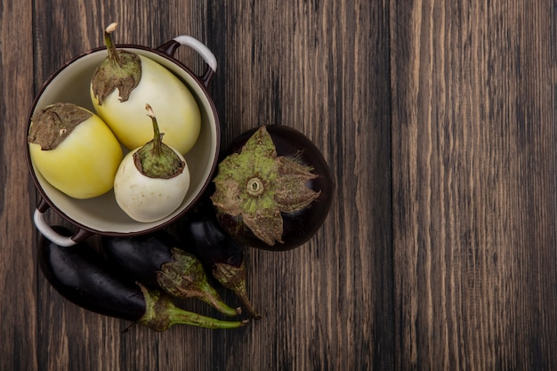 Bovenaanzicht kopie ruimte zwart-wit aubergine in een pan op houten achtergrond