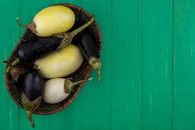 Bovenaanzicht kopie ruimte zwart-wit aubergine in mand op groene achtergrond
